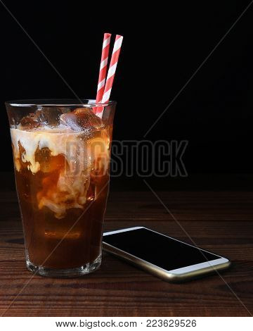 A glass of iced coffee with straws on a dark wood table. Fresh poured cream is permeating through the glass with a cell generic phone laying next to the glass. Vertical with copy space.