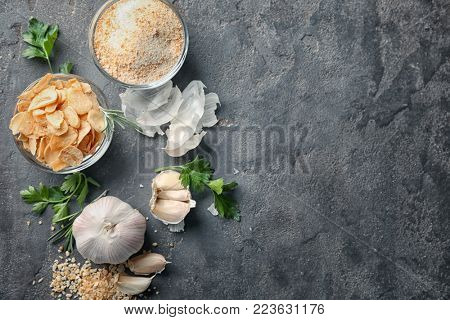 Dried garlic flakes, granules and powder on grey background