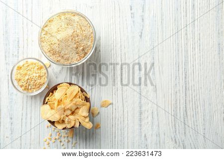 Dried garlic flakes, granules and powder in bowls on wooden background