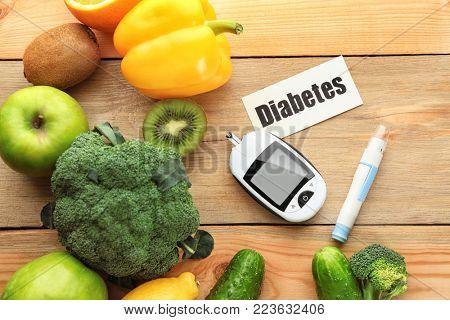 Digital glucometer, lancet pen,fruits and vegetables on wooden background. Diabetes diet