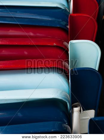 Closeup shot of a stack of battered folding metal chairs painted red, white and blue.
