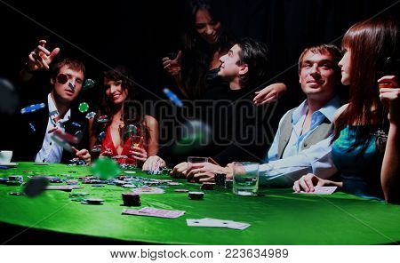 Young man throwing chips on the table while playing cards.
