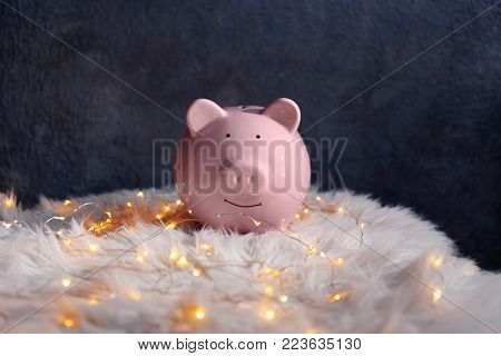 Piggy bank and Christmas garland on faux fur