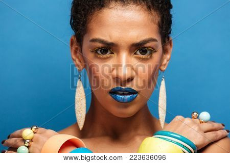 Colorful photo of strict serious mixed-race woman with trendy makeup and accessories posing with crossed hands on shoulders over blue wall