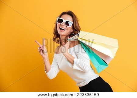 Image of happy young woman standing isolated over yellow background holding shopping bags. Looking camera showing peace gesture.