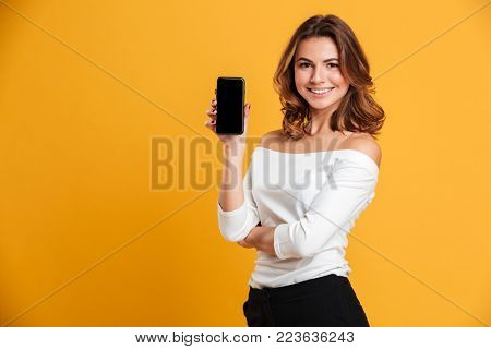 Image of smiling young woman standing isolated over yellow background. Looking camera showing display of mobile phone.