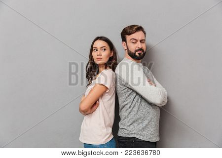 Portrait of an upset young couple standing back to back with arms folded over gray background