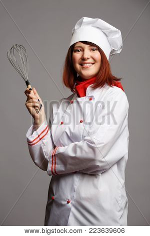 Image of woman cook in white robe and cap with whisk in hand