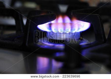closeup of gas stove burner, flame indicates dirty natural gas