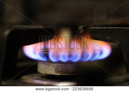 gas stove burner closeup, yellow flame indicates dirty natural gas