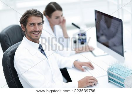 Young male technician working on computer in laboratory