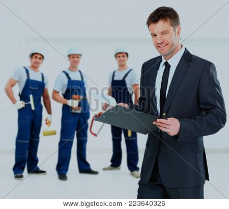 Owner on the background of the decorators holding construction tools.