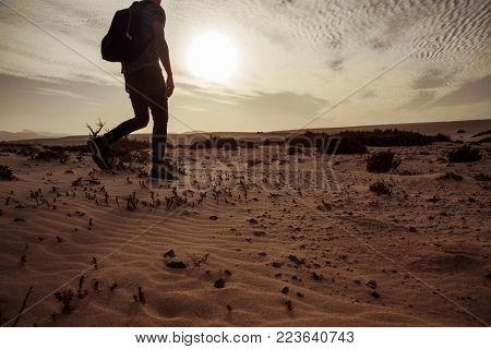 a young caucasian man seen from behind carrying a backpack, walking by the sand of a desert, in backlit at dusk