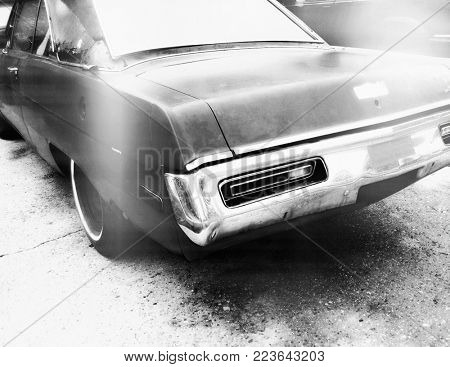 Black and White Instagram style filtered image of a rusted old American muscle car