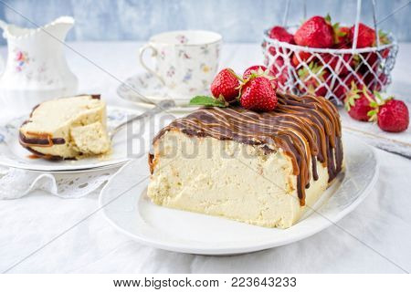 Traditional chocolate caramel cheesecake with fresh strawberries as top view on a plate