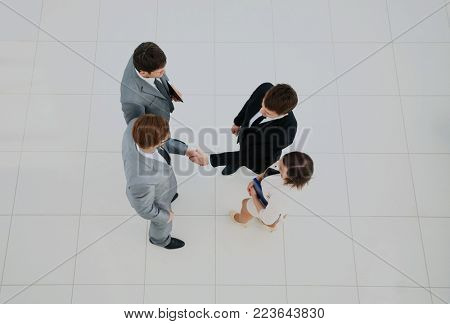 Business meeting. Top view of four people in formalwear standing close to each other while two of them handshaking.