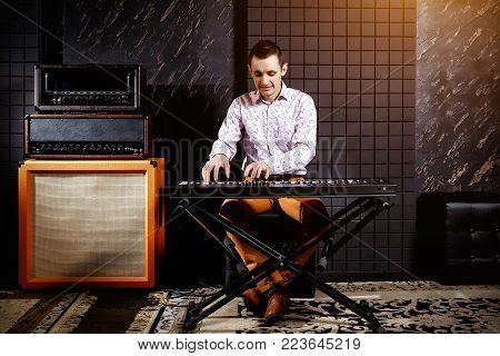 A musician in a light shirt plays a piano synthesizer in a dark recording studio. Amplifiers near