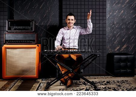 A musician in a light shirt plays a piano synthesizer in a dark recording studio. Amplifiers near. Raised hand