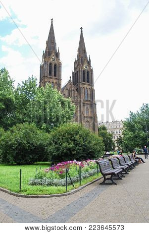PRAGUE, CZECH REPUBLIC - JULY 21, 2009 Green park alley with benches with the view of Church of Saint Ludmila, people rest on benches