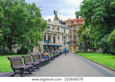 PRAGUE, CZECH REPUBLIC - JULY 21, 2009 Green park alley with benches with the view of Vinohrady Theatre (Dramatic Theater), people rest on benches