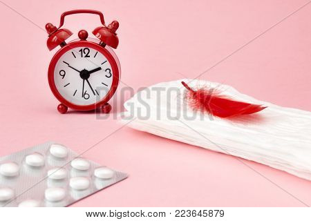 Menstrual pads, blood period calendar, clocks and pills. White pharmaceutical tablets. Menstruation period pain protection. Contraceptive, birth control hormone pills. Feminine hygiene products