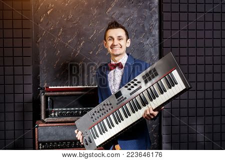 Musician in a blue jacket and red butterfly with a synthesizer in the hands at a recording studio, piano keyboard