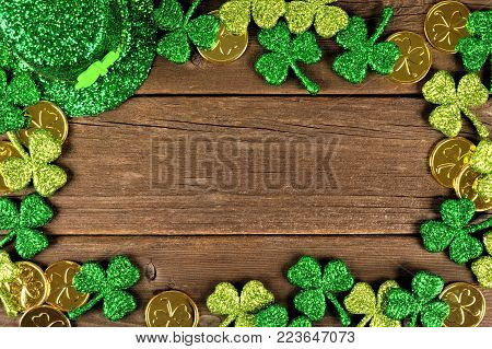 St Patricks Day frame of shamrocks, gold coins and leprechaun hat over rustic wood