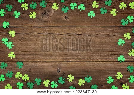 St Patricks Day frame of paper shamrocks over an old rustic wood background