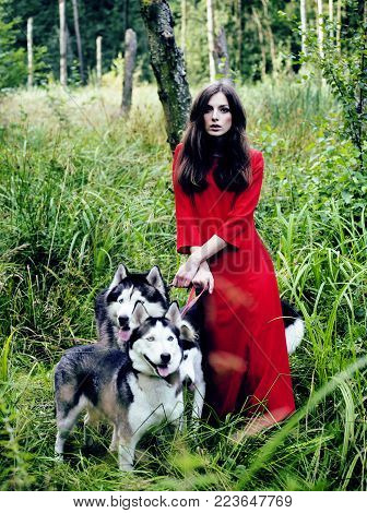 Mysterious woman in red dress with tree wolfs, forest, husky dogs mystery portrait, lifestyle people outside close up