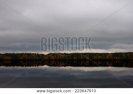 Gloomy autumn landscape near the calm waters of the river. Calm dark surface of the river, far away is an autumn forest, and the sky is gray, dark clouds.