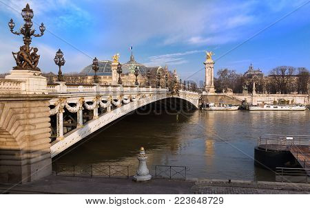 The bridge Alexandre III is a deck arch bridge that spans the Seine in Paris. It is widely regarded as the most ornate, extravagant bridge in the city. It is classified as French historic monument.