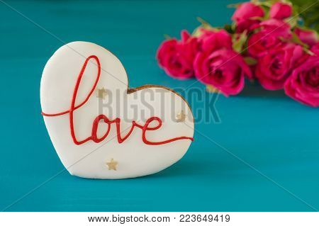 bouquet of roses and gingerbread in the shape of heart with the inscription love for holiday on wooden background. Mother's Day, Happy birthday , Women's Day. St. Valentines Day