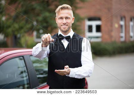 Portrait Of A Handsome Male Valet Holding Car Keys Outdoors