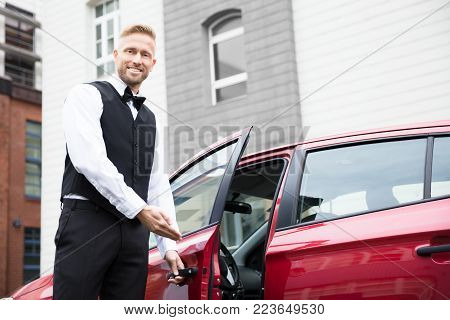 Portrait Of A Handsome Young Male Valet Opening Red Car Door