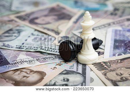 World money financial winning strategy, white winner chess king on international major countries banknotes, US dollar, Japanese yen, Euro, Chinese yuan.