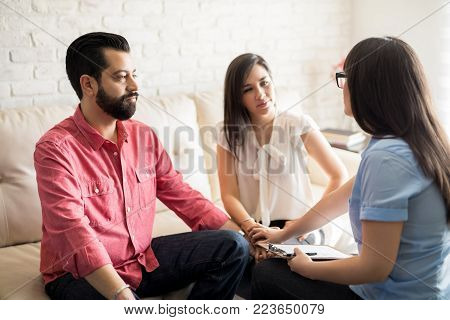 Relationship psychologist mediating couple thinking about divorce. Hispanic couple with problem in their relationship talking to family counselor.