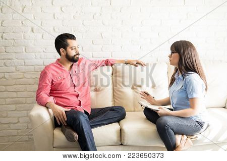 Female psychiatrist explaining diagnosis and treatment to male patient during therapy in her office