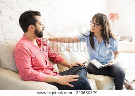 Concerned female psychotherapist comforting male patient in the office