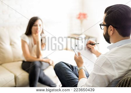 Psychologist writing notes during a session with woman patient. Psychotherapist with clipboard and female patient sitting in background.
