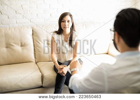 Beautiful hispanic female patient telling her troubles to psychologist