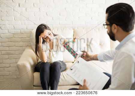 Crying woman sharing mental issues with male psychiatrist during therapy session, with therapist handing tissue box.