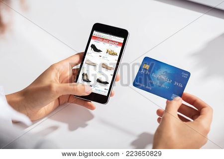 Close-up Of A Woman Holding Credit Card In Hand Doing Online Shopping Using Smart Phone