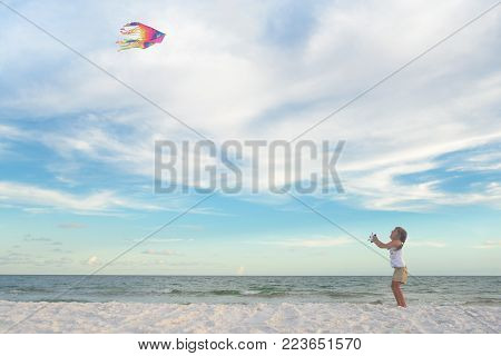 Happy girl on the sand flying kite high in summer sky, family vacation, beach activity