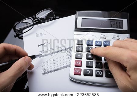 Close-up Of A Businessperson's Hand Calculating Invoice With Calculator