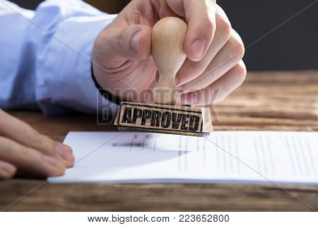 Close-up Of A Businessperson's Hand Stamping With Approved Stamp On Document
