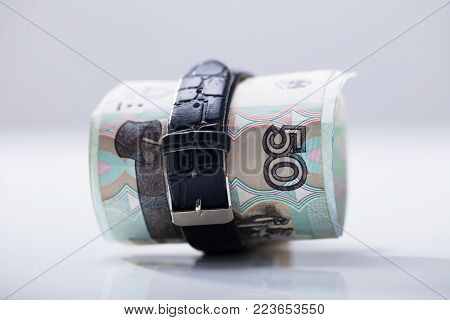 Rolled Up Russian Rubles Tied With Belt Against White Background