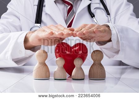 Doctor's Hand Protecting Wooden Family And Red Heart On White Desk