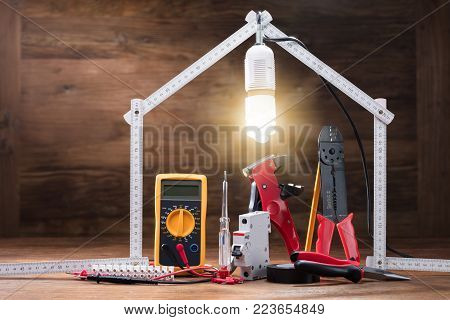 Repair Tools Under The Illuminated House Made With Measuring Tape On The Wooden Table
