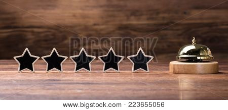 Black Five Stars Shape Arranged In Row With Service Bell On Wooden Table