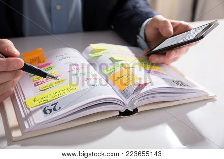 Close-up Of A Businessperson Holding Mobile Phone Writing Schedule In Diary
